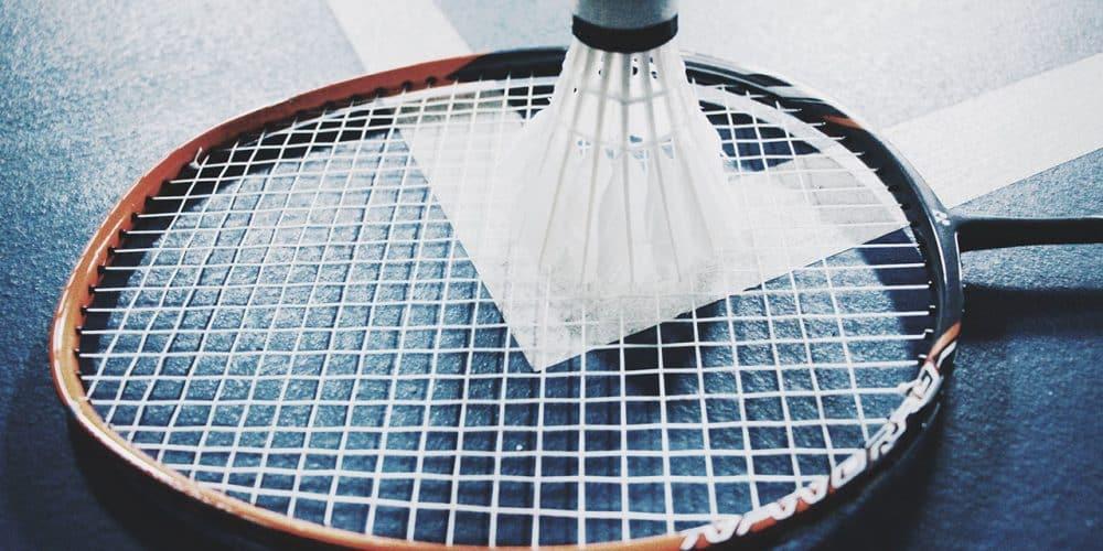 Ein Badminton Schläger mit einem Federball am Boden liegend.