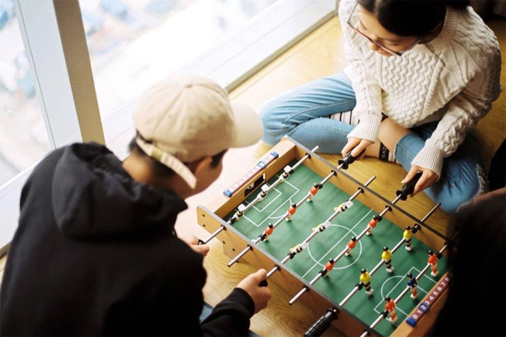 Ein Mann und eine Frau spielen Foosball, eine Art Miniaturwuzzler.