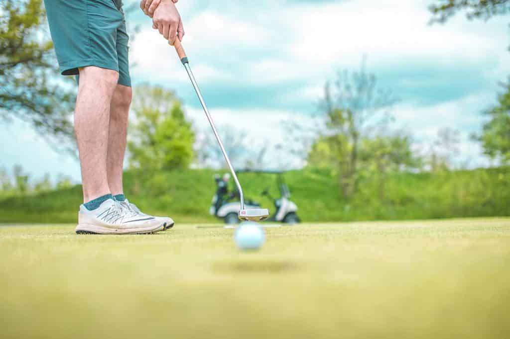 Ein weißer Mann mit grünen Hosen schießt einen Golfball ins Loch.