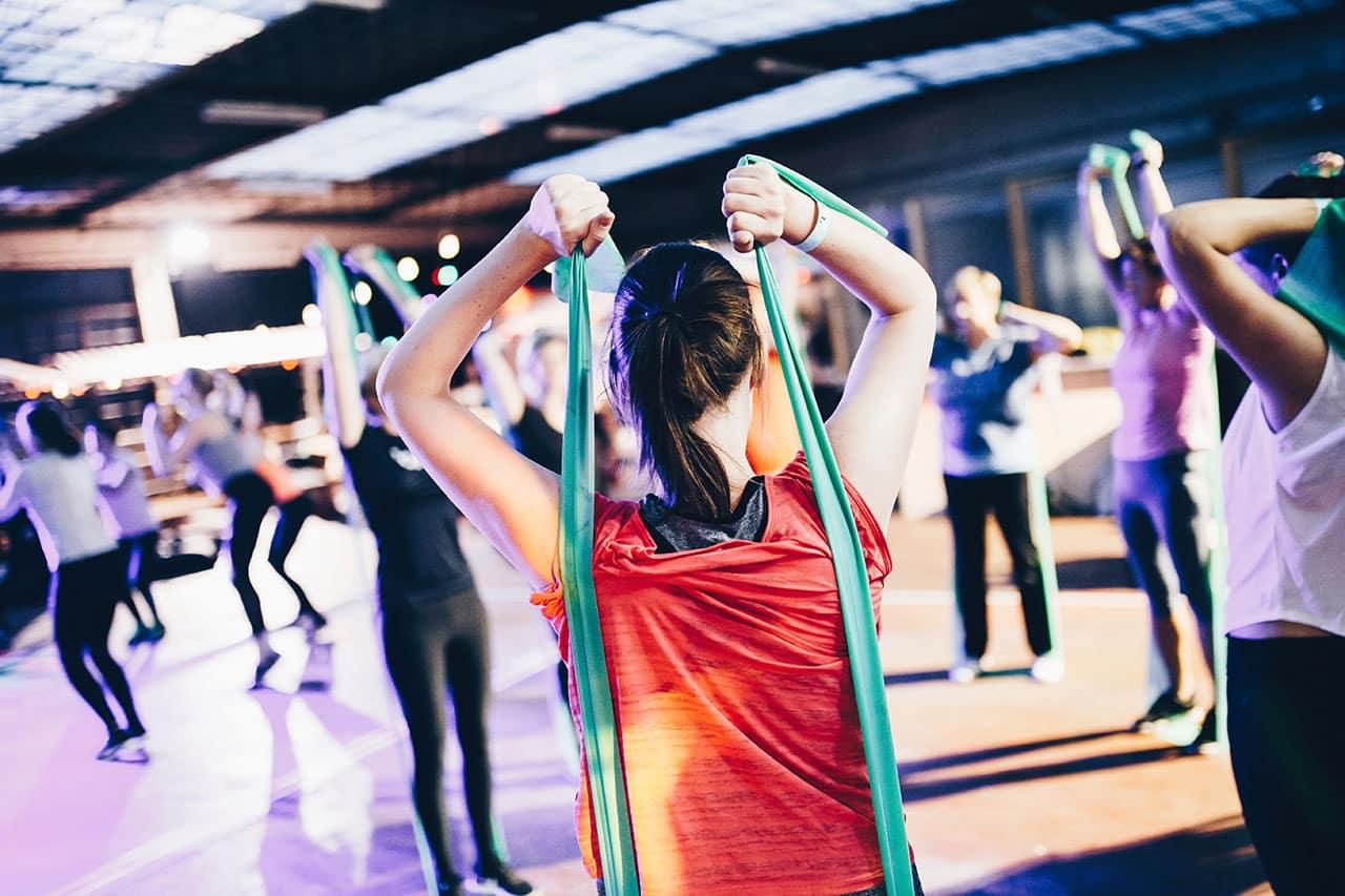 Eine Gruppe von Frauen, die gemeinsam mit Elastikbändern Gymnastik machen.