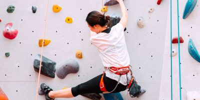 Eine schlanke Frau klettert eine gesicherte Indoor-Kletterwand hinauf.