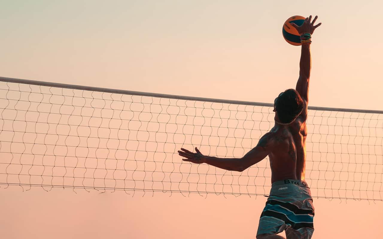 Beachvolleyball Spieler springt dem Ball entgegen