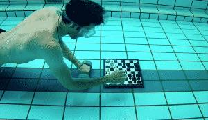 Mann spielt Schach unter Wasser, Brett und Figuren sind am Beckenboden befestigt, Mann trägt Taucherbrille, Juli 2019, Allsporthalle Eisenstadt