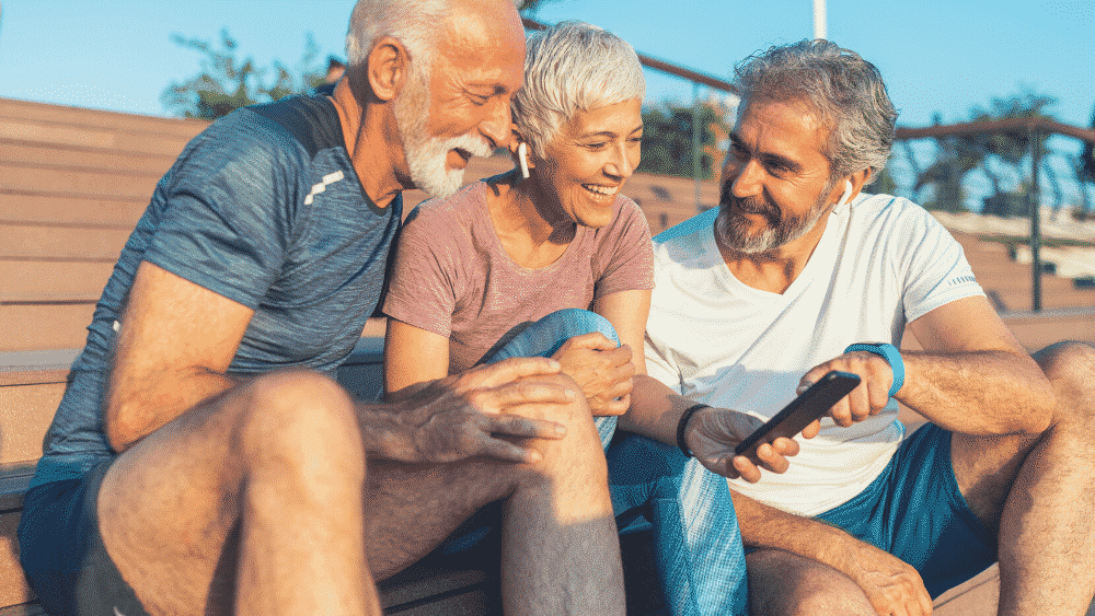 SportlerInnen mittleren Alters sitzen vor Tablet