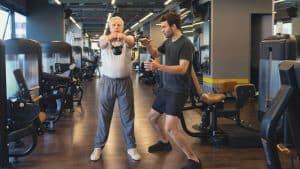 zwei Männer, die miteinander Sporttreiben, ambitioniert, Fitnesscenter