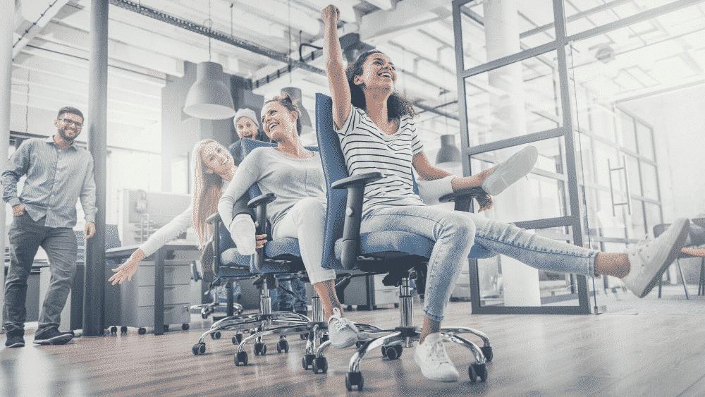 Bürogemeinschaft hat Spaß, fährt auf Bürosessel Rennen, Nudging