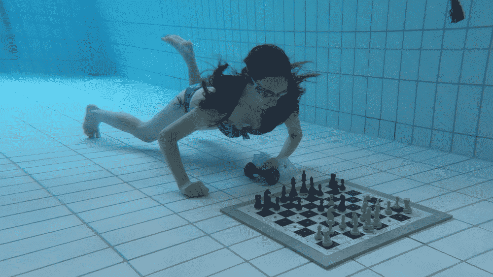 Schachspielerin taucht, spielt auf einem Schachbrett unter Wasser