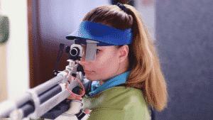 Sportschützin legt Luftgewehr an, Turnier