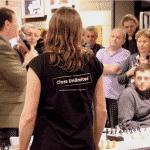 Dame steht vor Menge und hört Redner zu, Schachbretter im Hintergrund, Tshirt mit Chess Unimited Aufdruck