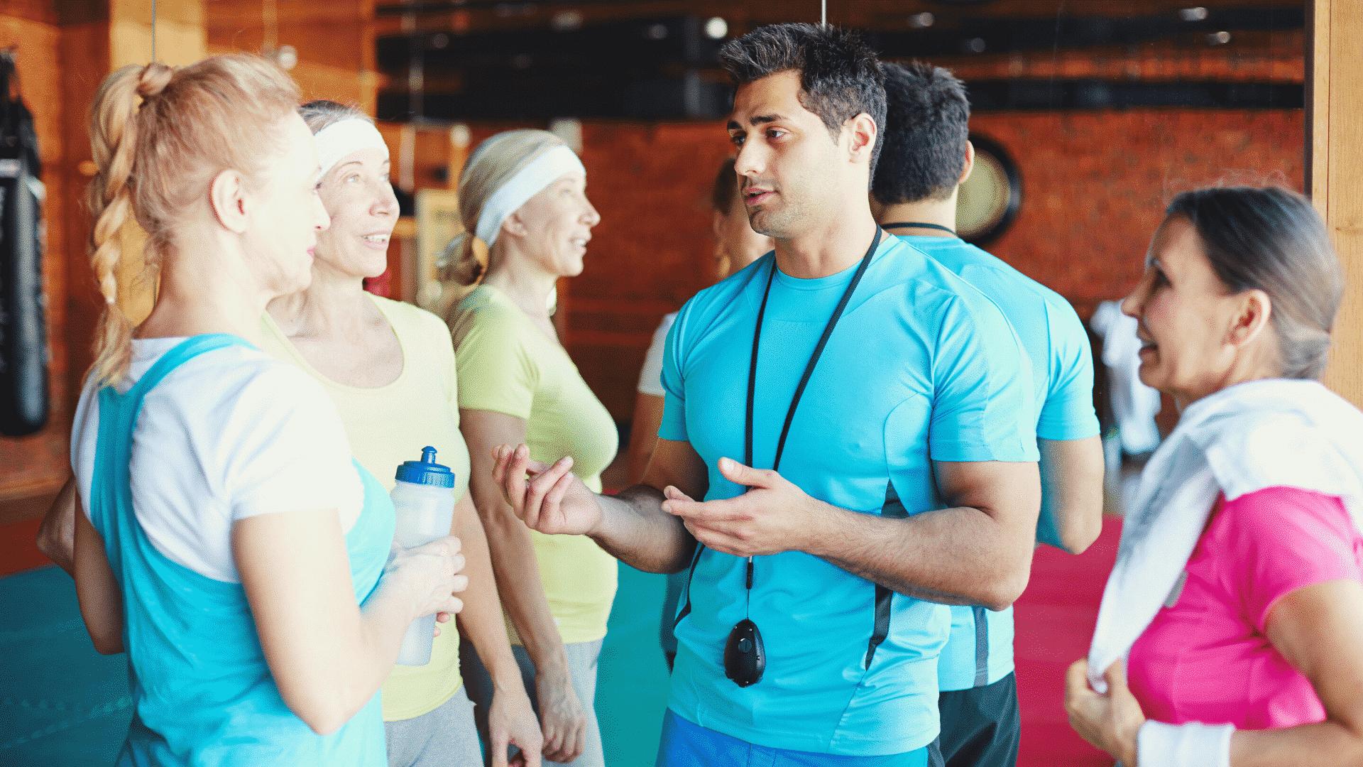 Sportgruppe steht um Trainer, Erklärung, Indoor