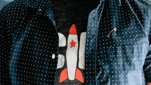 Mann trägt Tshirt mit Comicrackete drauf, nur Brust zu sehen