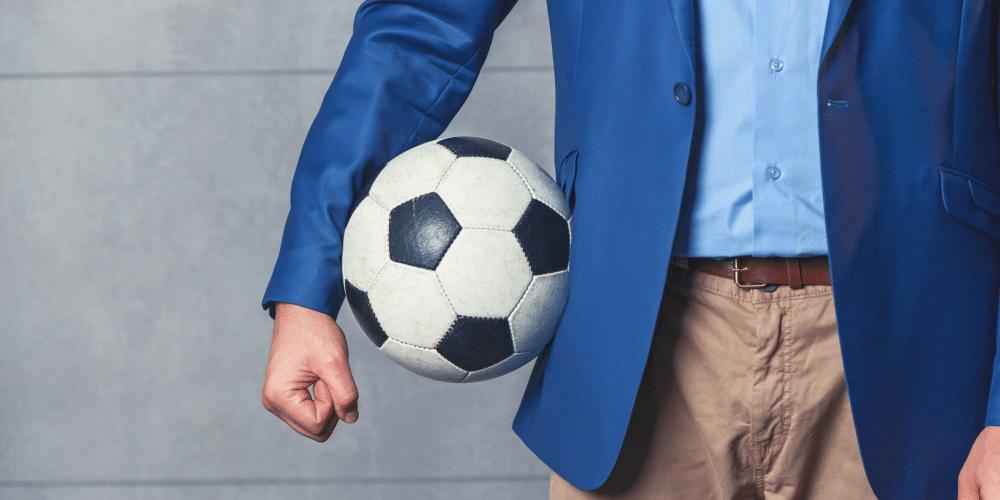 Mann in Sakko hält Fußball unter dem Arm