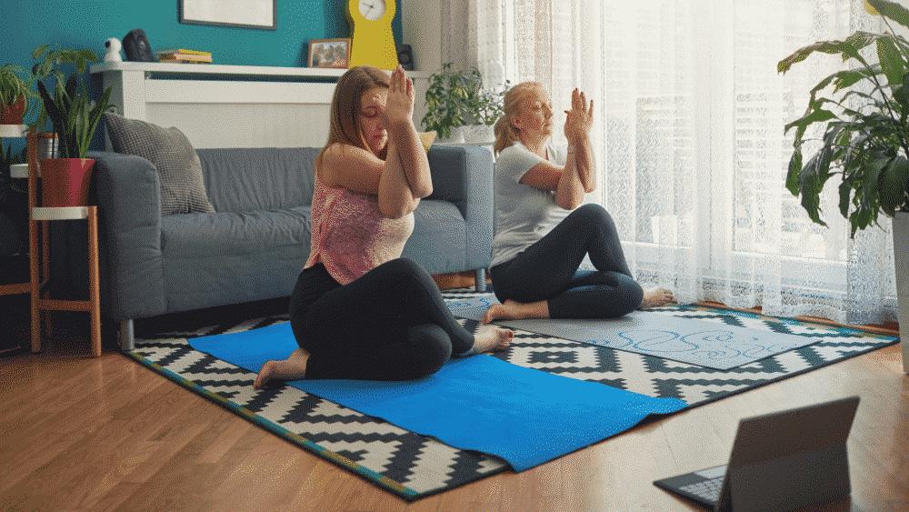 Yoga, zwei Damen, die zu Hause Yoga machen, online