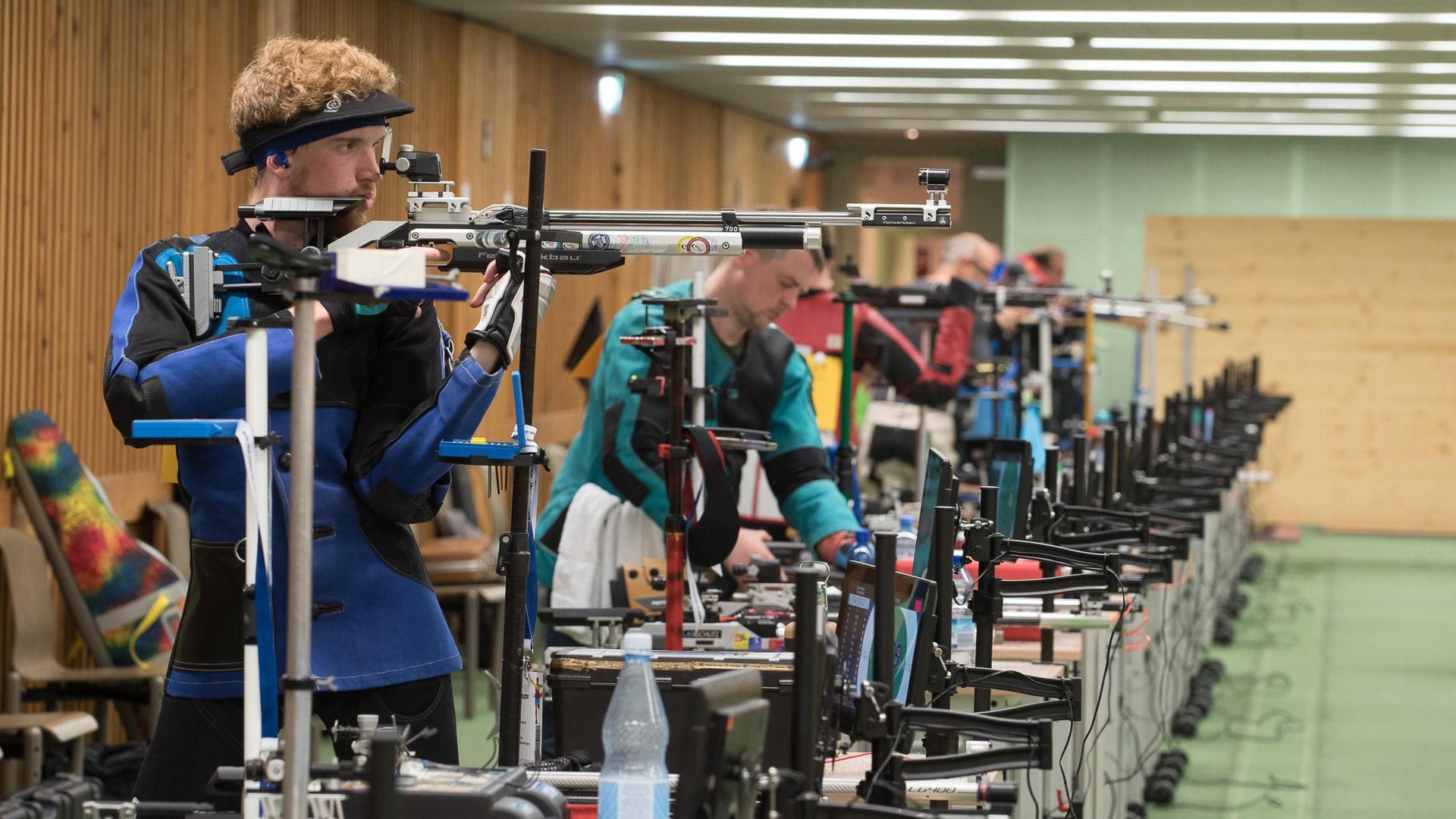 Mehrere Sportschützen am Luftgewehr, bereits aufgelegt, Konzentration, Betriebssport