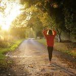 Frau die einen Weg entlang geht, Herbst, Sonne scheint