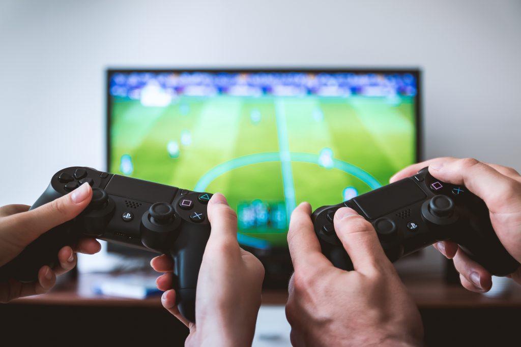 Playstation, FIFA, Mann und Frau spielen, keine Gesichter zu sehen